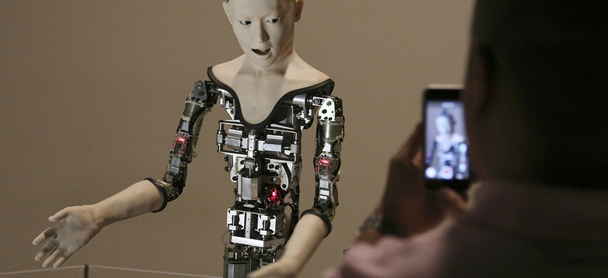 "A visitor takes photos of the humanoid robot ""Alter"" displayed at the National Museum of Emerging Science and Innovation in Tokyo, Monday, Aug. 1, 2016."
