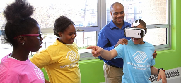 meer Washington, development associate at Boys & Girls Club of Newark assists a student with Samsung's Gear VR to help experience virtual reality at the Boys and Girls Club of Newark.