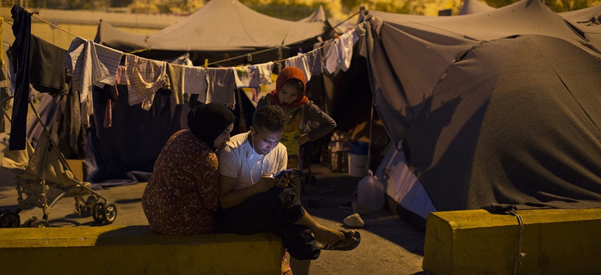 An Afghan family looks on a smart phone at the Athens' main Piraeus port, Friday, July 8, 2016.
