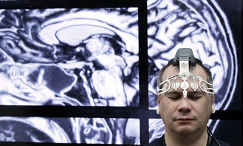 BrainScope employee Doug Oberly wears a brain scanning headset at the NFL owners' meeting in Boca Raton, Fla.