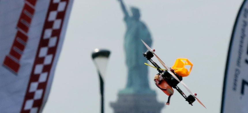 A pilot flies a small racing drone through an obstacle course on Governors Island in New York Harbor, Friday, Aug. 5, 2016.