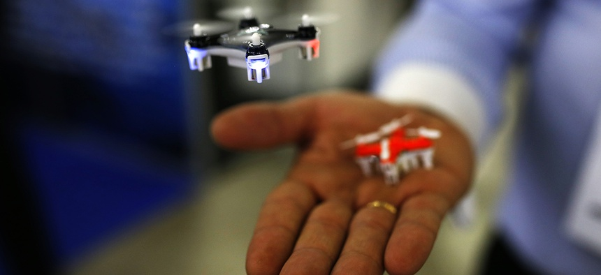 A man controls a mini drone during the Global Robot Expo fair in Madrid, Thursday, Jan. 28, 2016.