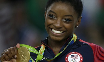 United States' Simone Biles displays her gold medal for floor during the artistic gymnastics women's apparatus final at the 2016 Summer Olympics.