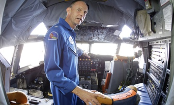 "U.S. Navy Capt. Harris Halverson, shown in this ultra wide angle photo, demonstrates some of the functions in the cockpit of the National Oceanic and Atmospheric Administration's P-3 turboprop aircraft ""Miss Piggy""."