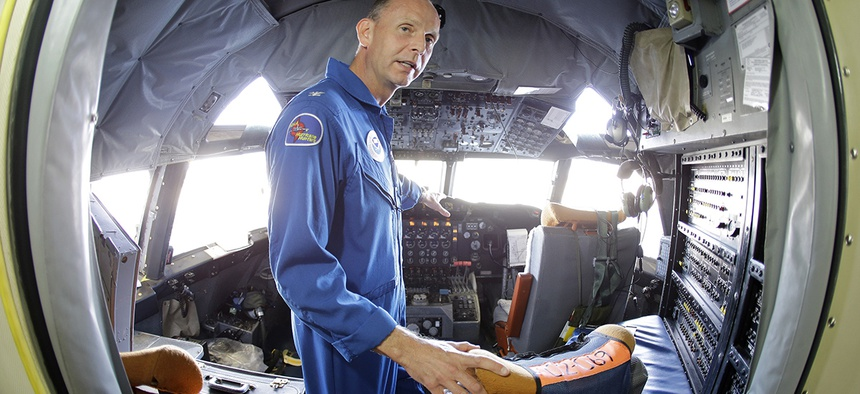 """U.S. Navy Capt. Harris Halverson, shown in this ultra wide angle photo, demonstrates some of the functions in the cockpit of the National Oceanic and Atmospheric Administration's P-3 turboprop aircraft """"Miss Piggy""""."""