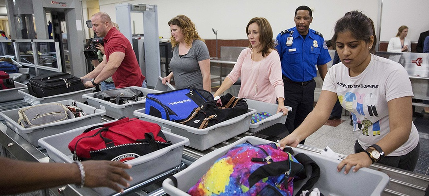 Passengers push their carry-on belongings onto an automated conveyer belt at a newly designed passenger screening lane unveiled at Hartsfield-Jackson Atlanta International Airport.