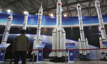 A visitor looks at the scale models of Chinese space rockets displayed at the China International Industry Fair in Shanghai, China.