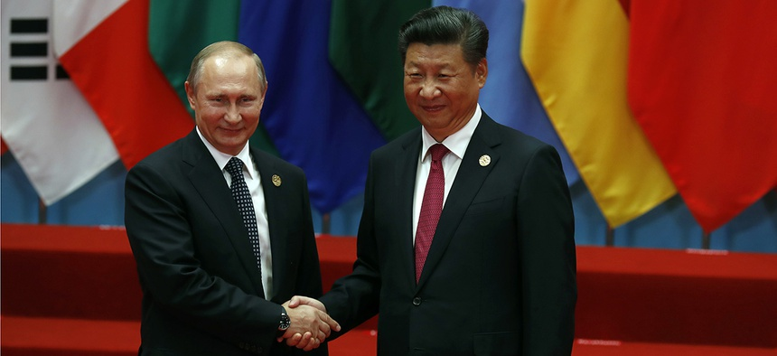 Russian President Vladimir Putin, left, shakes hands with Chinese President Xi Jinping.