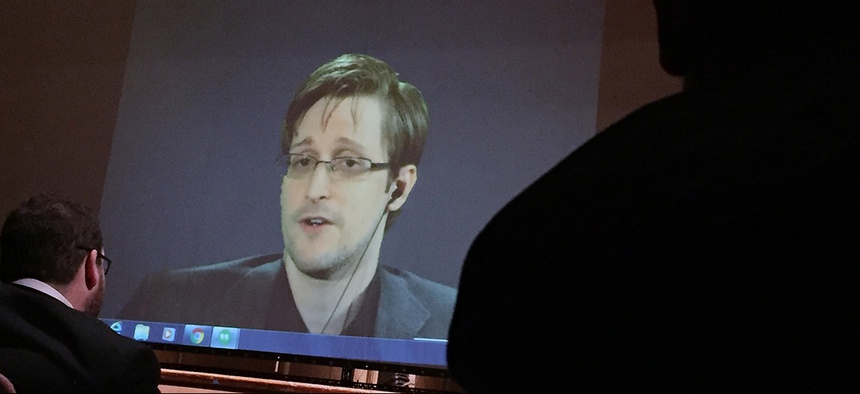 Former NSA contractor Edward Snowden, center speaks via video conference to people in the Johns Hopkins University auditorium, in Baltimore.