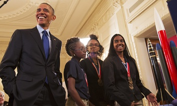 President Barack Obama laughs as Stephanie Bullock, 15, of Saint Croix, Virgin Islands, far right, explains her team's rocket design during the president's tour of the White House Science Fair, Monday, March 23, 2015.