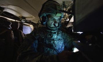 Specialist Matthew Syperda of the 3rd Brigade Combat Team, 1st Cavalry Division, looks at his cellular phone inside his unit's Mine Resistant Ambush Protected vehicle.