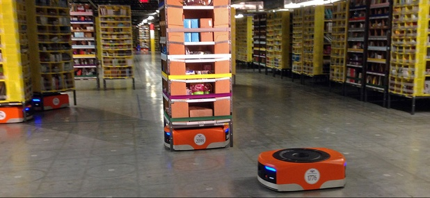 A Kiva robot drive unit is seen, foreground, before it moves under a stack of merchandise pods, seen on a tour of one of Amazon's newest distribution centers in Tracy, Calif.