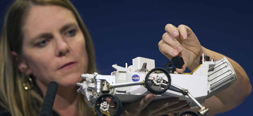 Jennifer Trosper, Mars Science Laboratory, MSL mission manager, JPL, adjusts the high-gain antenna on a rover model during a news briefing on the last data and imagery from Sol 1 at NASA's Jet Propulsion Laboratory.