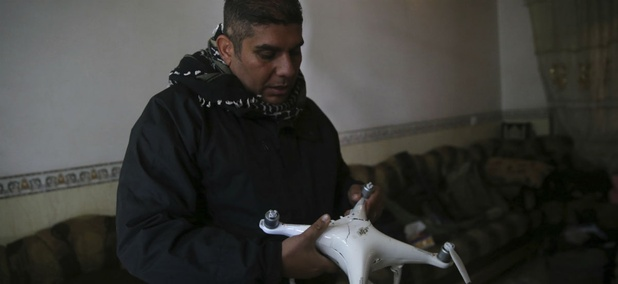 Iraqi special forces Lt. Col. Ali Hussein holds a destroyed drone used by Islamic State militants, which was shot down by his brigade, in the Bakr front line neighborhood, in Mosul, Iraq, Friday Nov. 25, 2016.