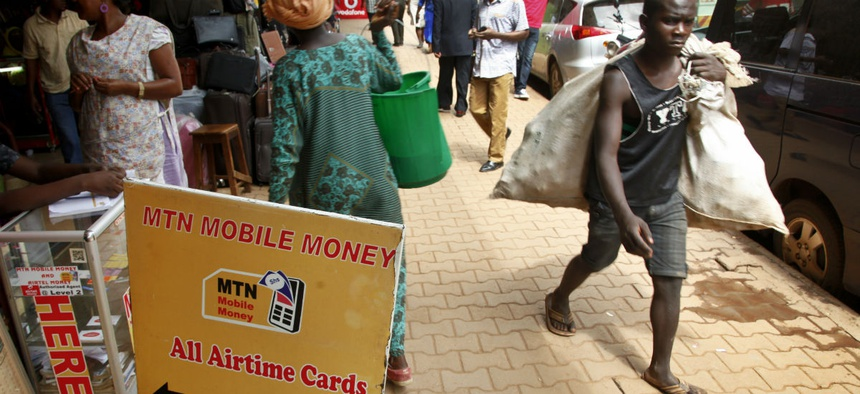 Pedestrians walk past a mobile money point in Kampala, Uganda.
