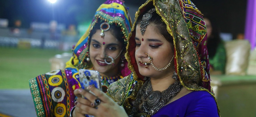 Indian girls in traditional attire, check a mobile phone after performing Garba, a traditional dance of Gujarat state on the first night of Hindu festival Navratri in Ahmadabad.