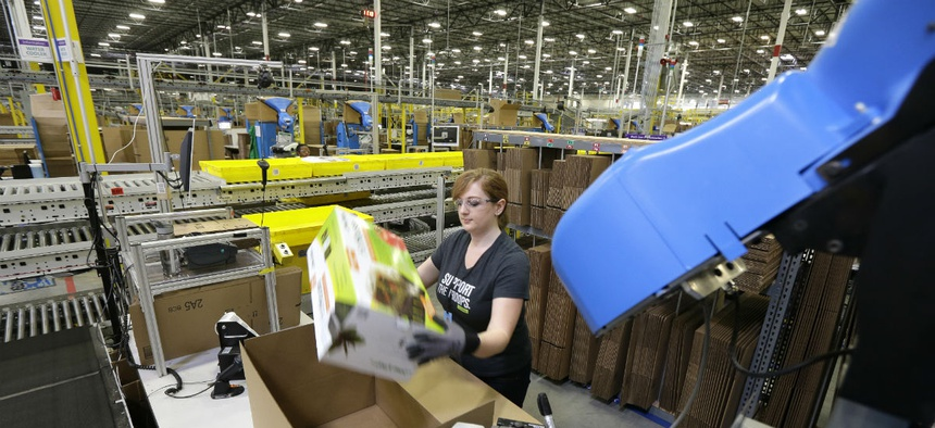 A worker places an item in a box for shipment,at a Amazon.com fulfillment center in DuPont, Wash.