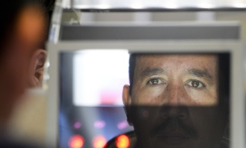 A pedestrian crossing from Mexico into the United States at the Otay Mesa port of entry has his facial features and eyes scanned at a biometric kiosk Thursday, Dec. 10, 2015, in San Diego.