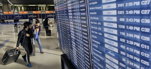 Travelers walk past an airline reader board Tuesday, Nov. 22, 2016, at Logan International Airport, in Boston.