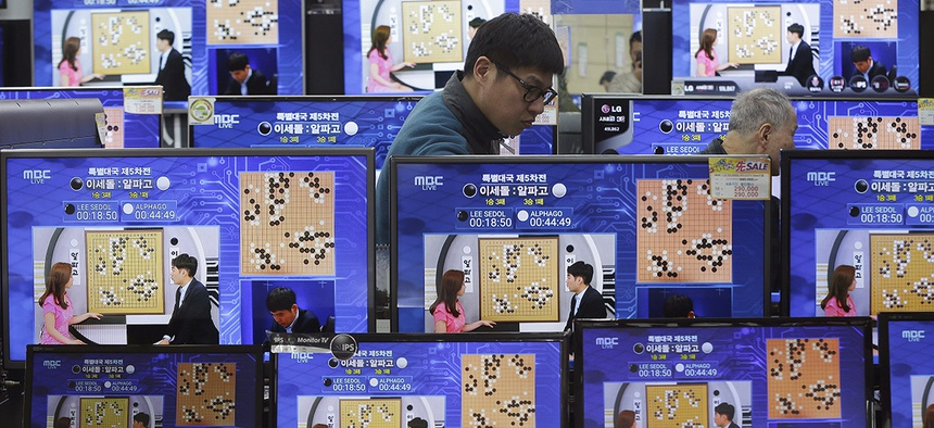 TV screens show the live broadcast of the Google DeepMind Challenge Match between Google's artificial intelligence program, AlphaGo, and South Korean professional Go player Lee Sedol.