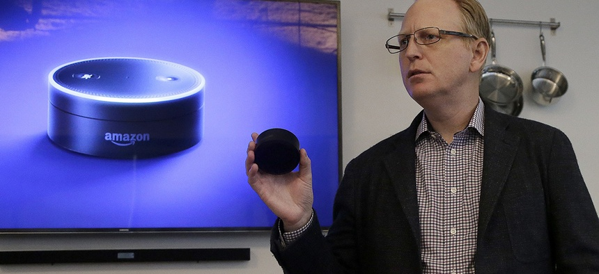 David Limp, Amazon Senior Vice President of Devices, holds an Echo Dot while speaking in San Francisco.