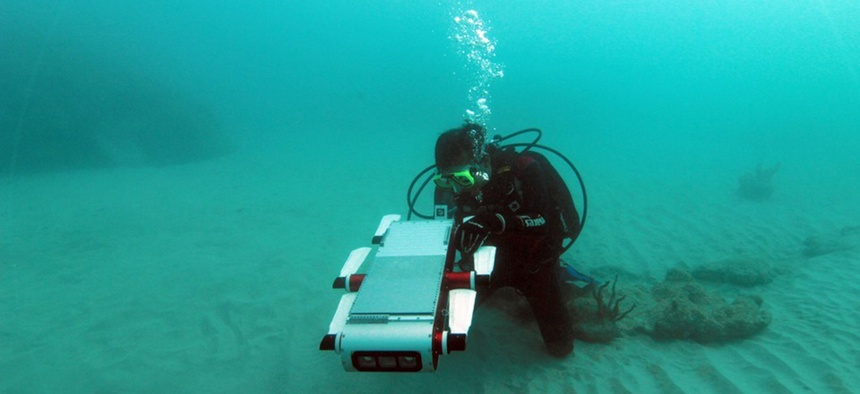 """Yogesh Girdhar, a researcher at Woods Hole Oceanographic Institute, swims with a """"curious"""" robot he helped build."""
