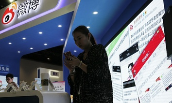 A woman browses her smartphone near a display booth for China's Weibo microblogging website at the 2016 Global Mobile Internet Conference in Beijing, April 28, 2016.