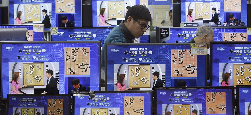 TV screens show the live broadcast of the Google DeepMind Challenge