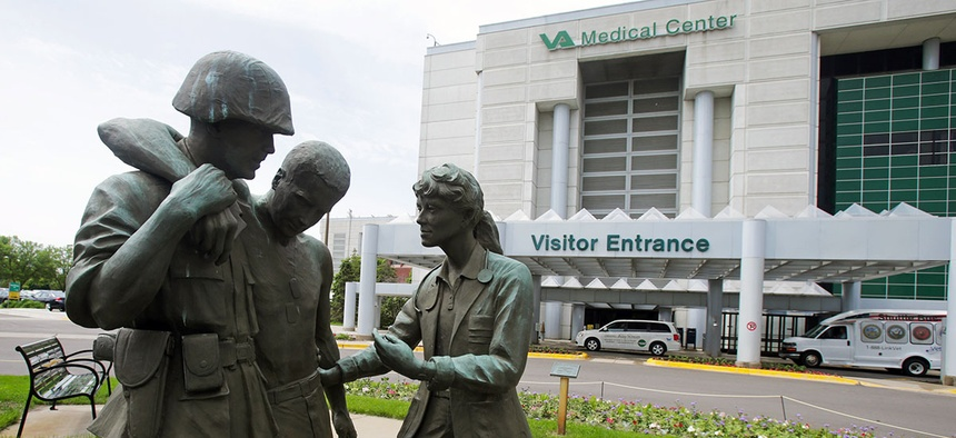Three statues portraying a wounded soldier being helped, stand on the grounds of the Minneapolis VA Hospital, Monday, June 9, 2014.