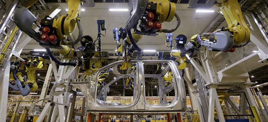 Robots fasten parts on a new 2015 aluminum-alloy body Ford F-150 truck in the body shop at the company's Kansas City Assembly Plant in Claycomo, Mo.