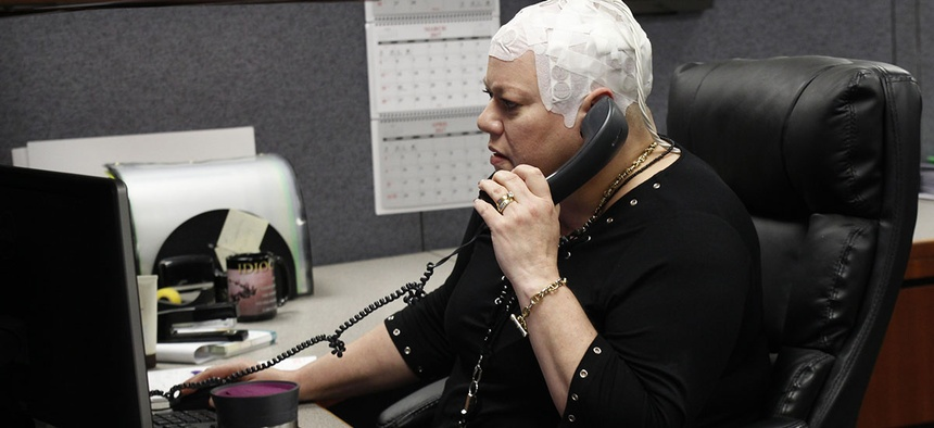 Joyce Endresen wears an Optune therapy device for brain cancer, as she speaks on a phone at work in Aurora, Ill.