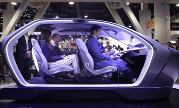 Show attendees sit in the Chrysler Portal self-driving concept car at CES International Thursday, Jan. 5, 2017, in Las Vegas.