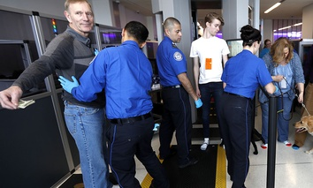 A traveler, left, is padded by a TSA agent as trainers, top right, lead their service dogs through the security area at Newark Liberty International Airport while taking part of a training exercise, Saturday, April 1, 2017