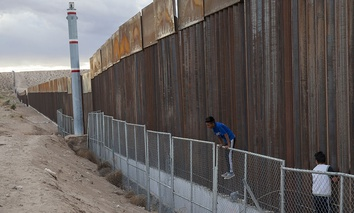 Children play on two fences marking the U.S.-Mexico border, in the Anapra neighborhood of Ciudad Juarez, Mexico, Wednesday, March 29, 2017.