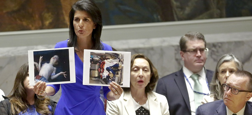 Nikki Haley, United States' Ambassador United Nations, shows pictures of Syrian victims of chemical attacks as she addresses a meeting of the Security Council on Syria at U.N. headquarters.