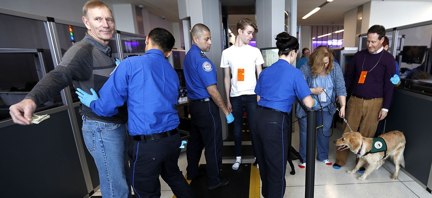 A traveler, left, is padded by a TSA agent as trainers, top right, lead their service dogs through the security area at Newark Liberty International Airport while taking part of a training exercise, Saturday, April 1, 2017.