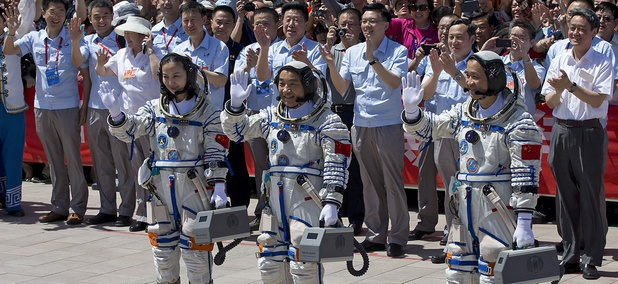 China's astronauts from left, Wang Yaping, Zhang Xiaoguang and Nie Haisheng wave as they leave the Jiuquan satellite launch center near Jiuquan in western China's Gansu province, June 2013.