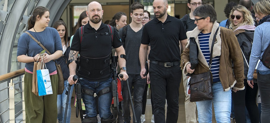 Paraplegic Dale Messenger, second from left, walks with the help of the robotic exoskeleton Ekso GT, on March 16, 2017.