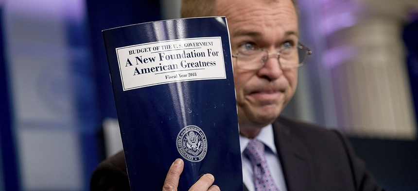 Budget Director Mick Mulvaney holds up a copy of President Donald Trump's proposed fiscal 2018 federal budget.