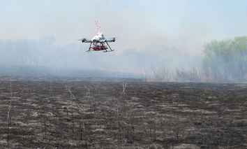 A drone designed to ignite controlled grass fires comes in for a landing in a field at the Homestead Monument of America in Beatrice, Neb., on Friday, April 22, 2016.