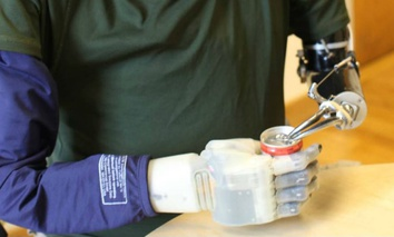 A participant in DARPA's Revolutionizing Prosthetics program tries opening a can.
