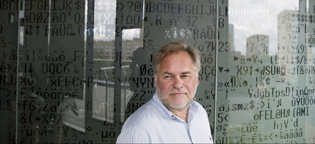 Eugene Kaspersky, Russian antivirus programs developer and chief executive of Russia's Kaspersky Lab, stands in front of a window decorated with programming code's symbols at his company's headquarters in Moscow, Russia, Saturday, July 1, 2017.