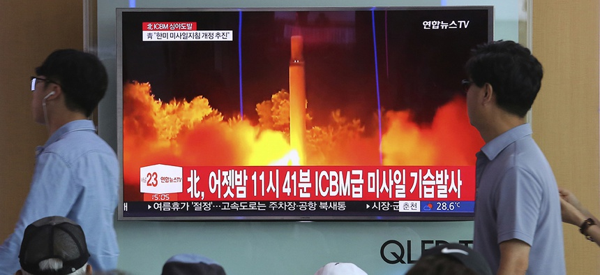 People watch a TV news program showing an image of North Korea's latest test launch of an intercontinental ballistic missile (ICBM), at the Seoul Railway Station in Seoul, South Korea, Saturday, July 29, 2017.