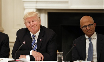 President Donald Trump, center, smiles as he is seated between Tim Cook, Chief Executive Officer of Apple, left, and Satya Nadella, Chief Executive Officer of Microsoft, right, during an American Technology Council roundtable.