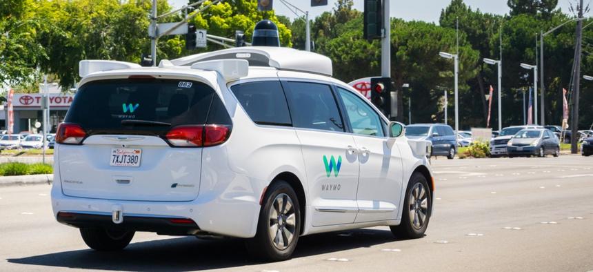 Waymo self-driving car cruising on a street in August.