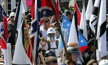 White nationalist demonstrators walk into the entrance of Lee Park surrounded by counter demonstrators in Charlottesville, Va., Saturday, Aug. 12, 2017.
