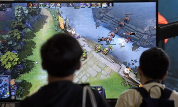 A monitor shows the game as fans look on at KeyArena during the International Dota 2 Championships Wednesday, Aug. 9, 2017, in Seattle.