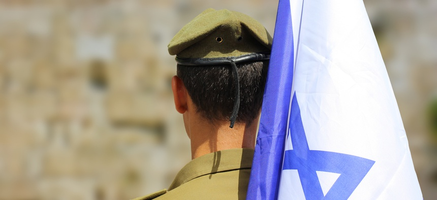 Israeli soldier with flag of Israel on blurred background of Western Wall.