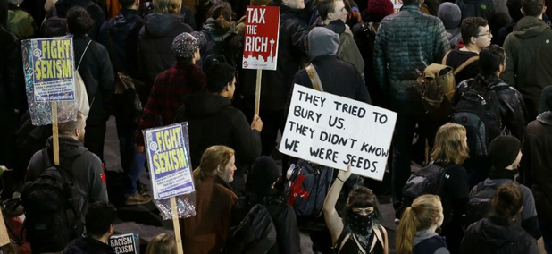 Protesters hold signs during a protest march against President Donald Trump, Friday, Jan. 20, 2017, in Seattle.