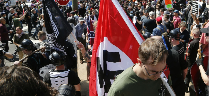 A man carries a Nazi flag into the entrance to Emancipation Park in Charlottesville, Va., Sat. Aug. 12, 2017.